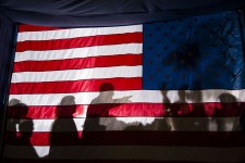 Barack_Obama_silhouetted_behind_flag_in_Dubuque