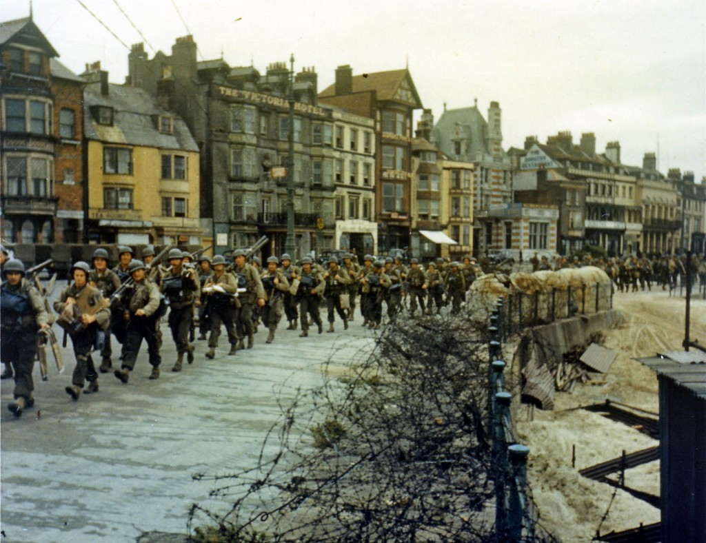 American troops marching through a British port town on their way to the docks. (June 1944). Source: Center of Military History.