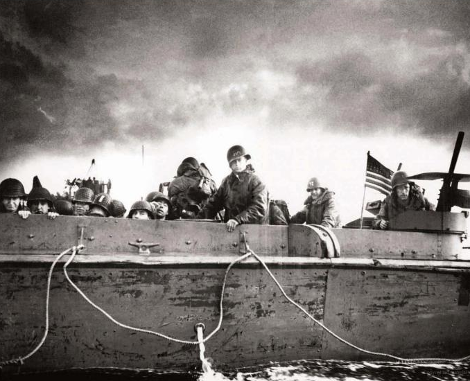 "A U.S. Coast Guard coxswain named ""Jim"" is at the helm of a landing craft vehicle carrying troops from the 4th Infantry Division toward Utah Beach on D-Day. Source: U.S. National Archives, # 26-G-2349."