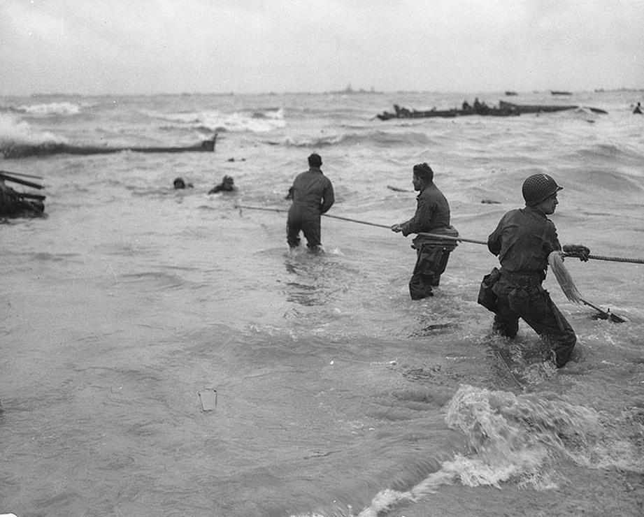 U.S. troops rescue men from a sunken landing craft on D-Day. (June 6, 1944). Source: U.S. National Archives, # SC 320869.