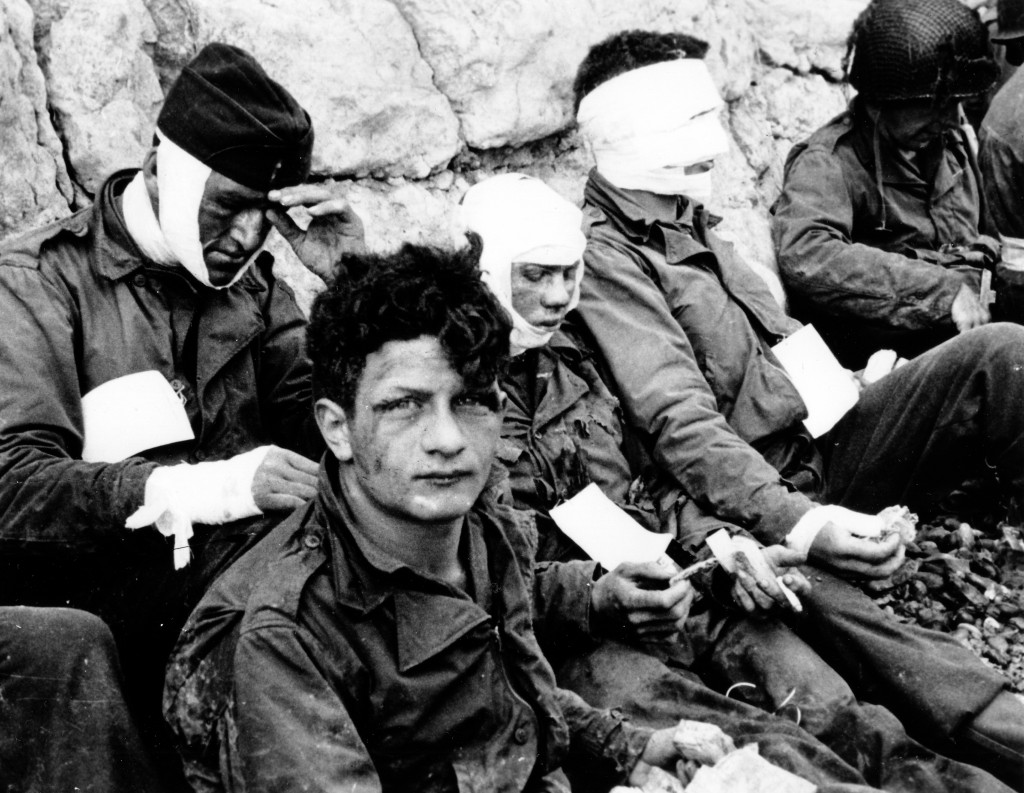 Wounded U.S. troops of the 3rd Battalion, 16th Infantry Regiment, 1st U.S. Infantry Division, receive cigarettes and food after they stormed Omaha Beach. Colleville-sur-Mer, Normandy, France. (June 6, 1944). Source: U.S. National Archives, SC 189910-S.