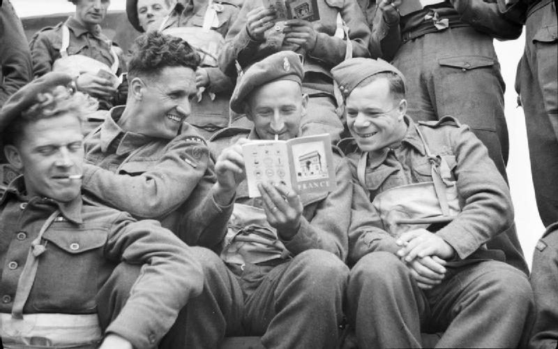 Final Embarkation: 3 British soldiers of 51st Highland Division in a landing craft pass the time by reading a booklet on France which they were issued before embarkation. (June 6, 1944). Source: Imperial War Museums,  B 5207.