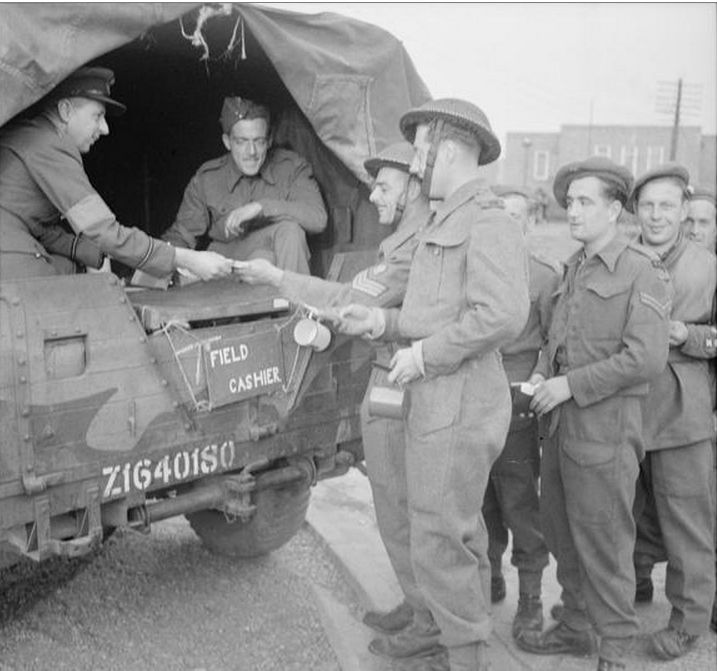 Royal Engineers of the 693 Road Construction Co. line up at a Field Cashiers office in the UK to exchange English money for French currency. (June 1, 1944). Source: Imperial War Museums, B 5149.