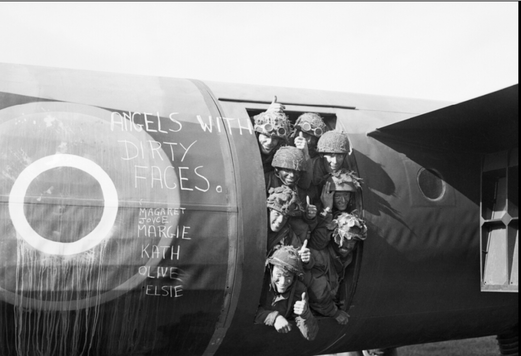 """Angels with dirty faces"" --Airborne troops smile from their Horsa glider as they prepare to fly out as part of the second drop on Normandy on the night of D-Day. (June 6, 1944). Source: Imperial War Museums, H 39182."