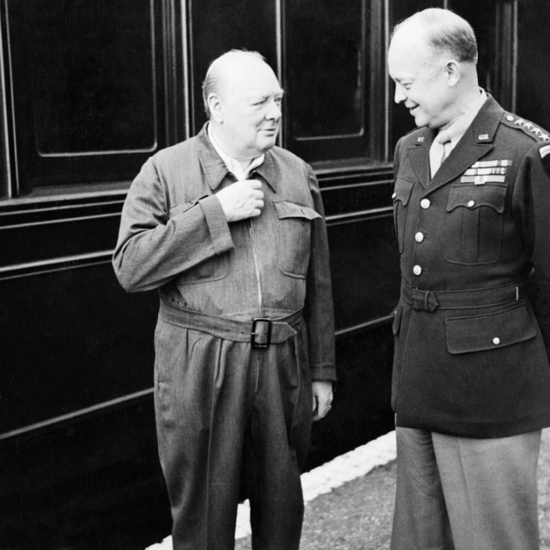 "Winston Churchill shows off his famous ""siren suit"" to General Dwight D Eisenhower, during a tour of Allied invasion forces in Kent. (May 12, 1944). Source: Imperial War Museums, # H 38458."