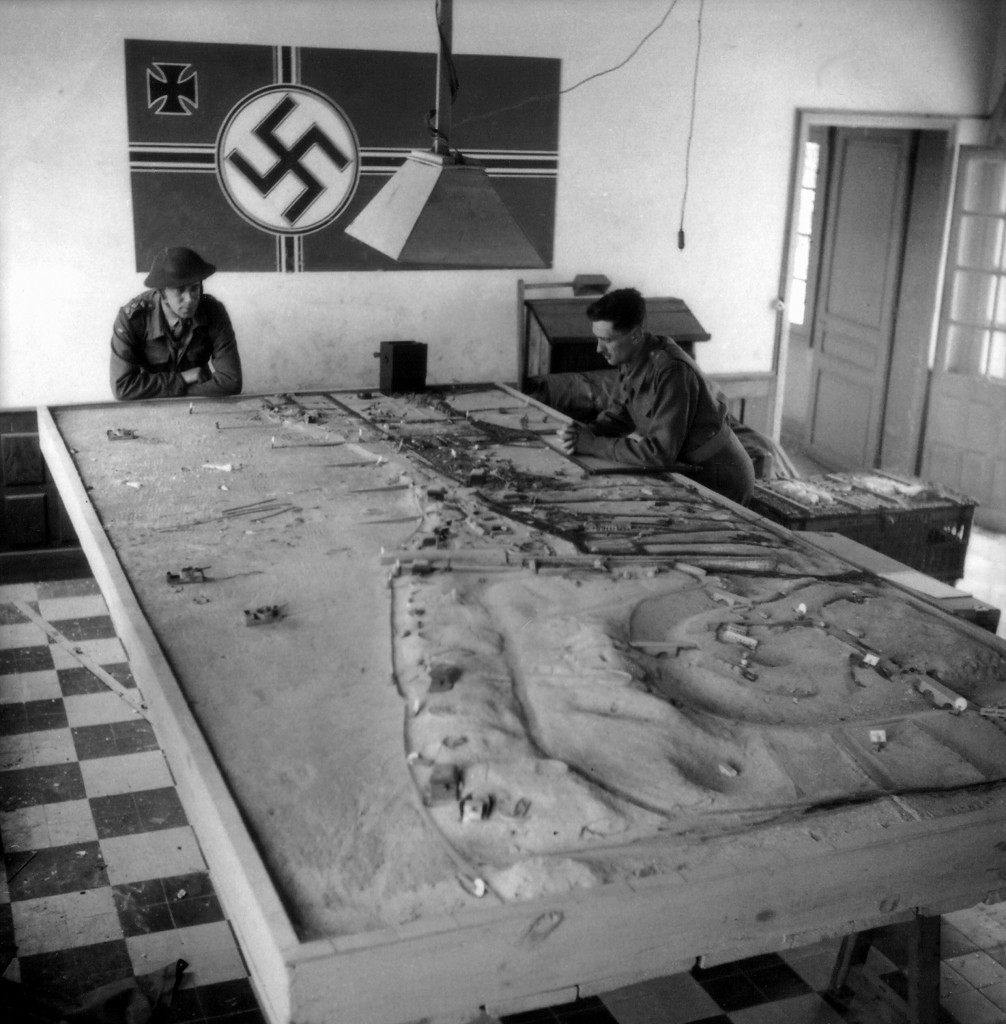 Two Canadian soldiers looking at a German model of defenses at Courseulles sur Mer. Juno Beach, Normandy, France. (June 6, 1944). Source: World War II Database.