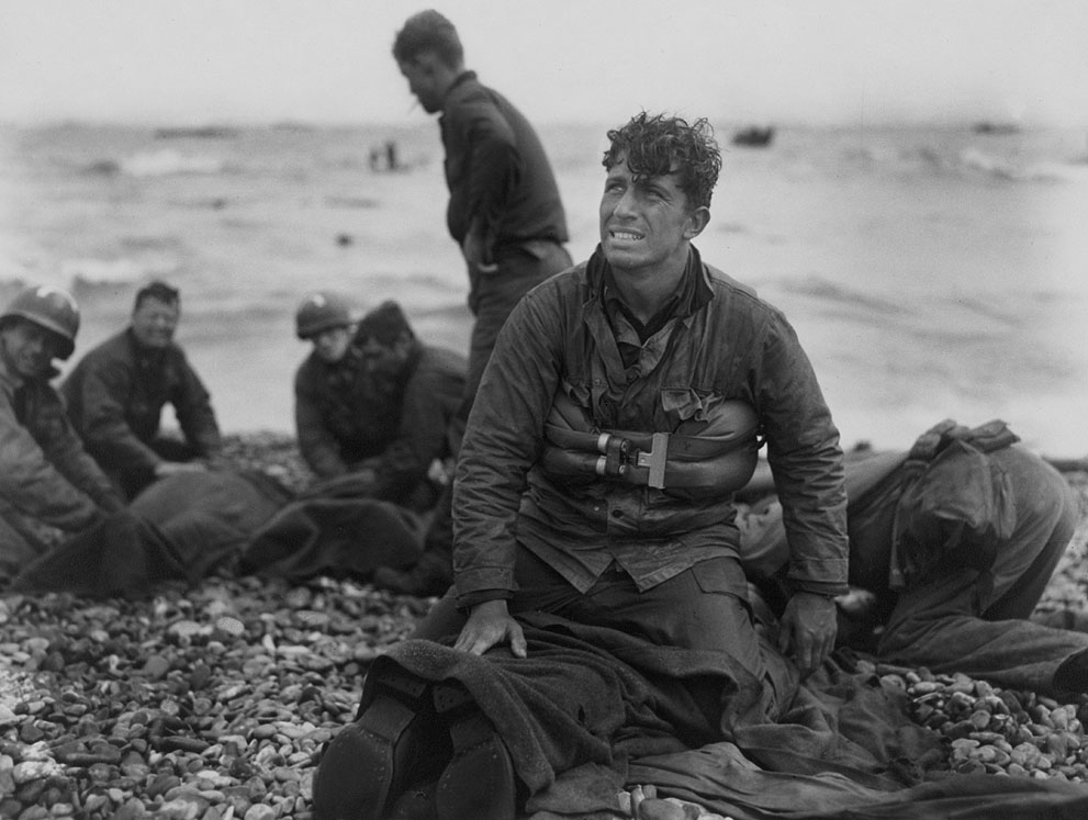 U.S. Army soldiers recovering remains of comrades at Omaha Beach, Normandy, France. (June 6, 1944). Source: U.S. Library of Congress, Photographer: Walter Rosenblum.