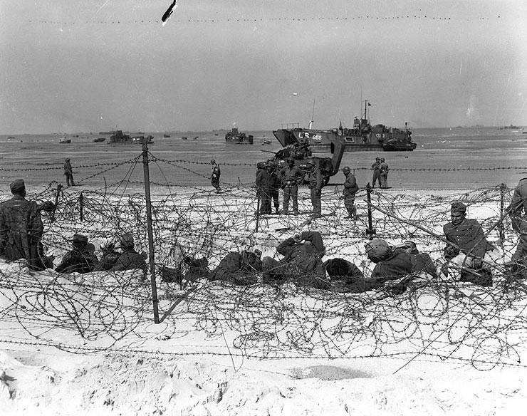 German prisoners of war in a barbed-wire enclosure on Utah Beach, Normandy. (June 6, 1944). Source: U.S. National Archives, # SC 320897.