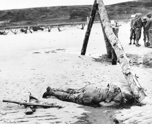 Crossed rifles in the sand are a comrade's tribute to this American soldier who sprang ashore from a landing barge and died on Omaha Beach. (June 6, 1944). Source: U.S. National Archives, #26-G-2397.