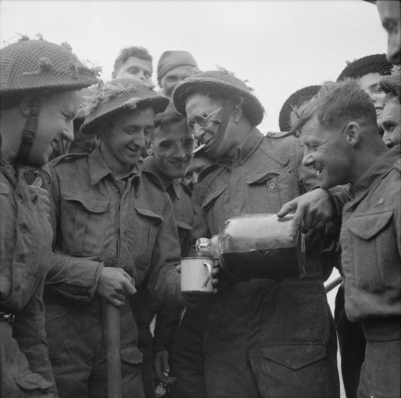 Lance Corporal Walter Ray, Royal Engineers, shares with other Beach Group personnel a bottle of rum he found floating in the sea, Gold area. (June 6, 1944). Source: Imperial War Museums, # B 5260.