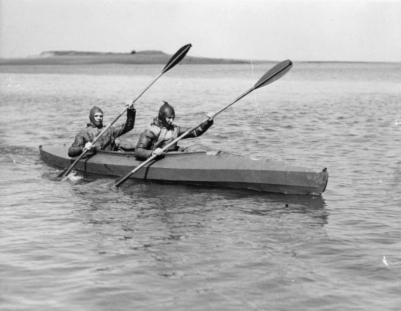 2 British Navy frogmen paddle 1 of the canoes; they were the underwater experts who blasted a hole in the Nazi's Atlantic Wall to enable invasion crafts to reach the Normandy beaches on D-Day. Source: Imperial War Museums, # A 30325.