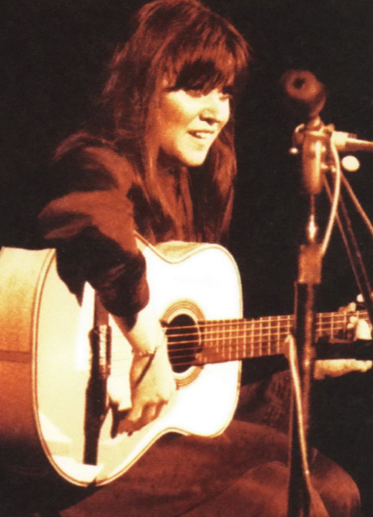 Melanie Safka plays the guitar on the first day of the original Woodstock Festival. (1969). Source: Woodstock Wikia.
