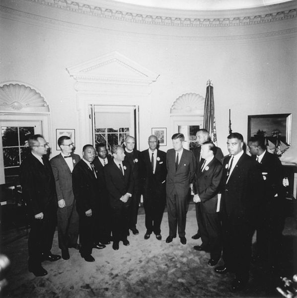 Photograph of President's meeting with March leaders, left to right: Willard Wirtz, Martin Luther King, Jr, Eugene Carson Blake, John F. Kennedy, Lyndon B. Johnson, Walter Reuther. (Aug. 28, 1963). Source: U.S. National Archives #194276.