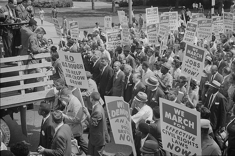 Photograph showing civil rights leaders, including MLK, surrounded by crowds carrying signs. Photographed by Warren K. Leffler. (Aug. 28, 1963). Source: Library of Congress #LC-DIG-ppmsca-04297.