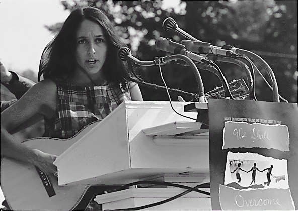 """Joan Baez. A sign hanging near the microphones reads """"We Shall Overcome."""" (Aug. 28, 1963). Source: U.S. National Archives #542017."""