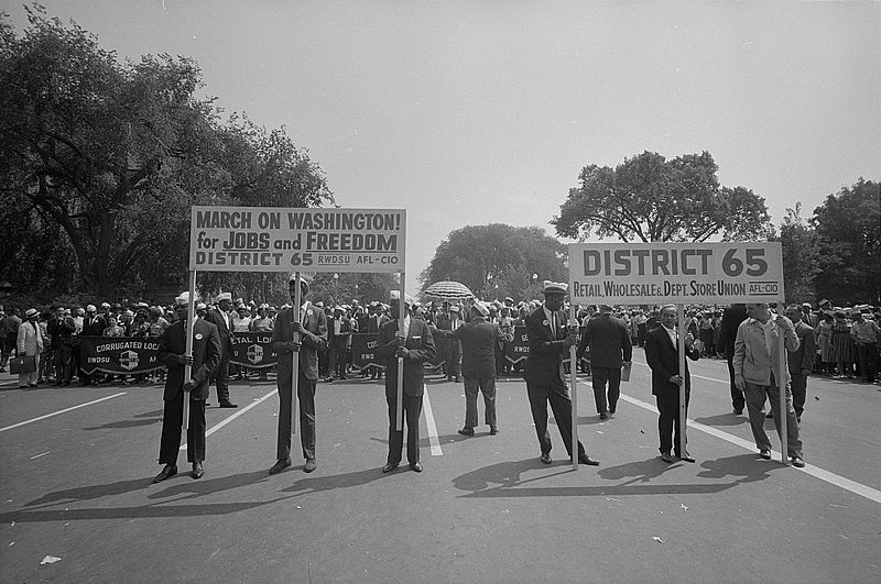 "Marchers carrying ""District 65"" sign at the March. Photographed by Marion S. Trikosko. (Aug. 28, 1963). Source: Library of Congress #LC-DIG-ppmsca-37247."