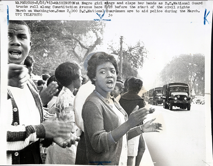 Girl sings and claps her hands as D.C. National Guard trucks roll along Constitution Ave.... (Aug. 28, 1963). Source: United Press International, New York World-Telegram & the Sun Newspaper Photograph Collection, Library of Congress #038.00.00.