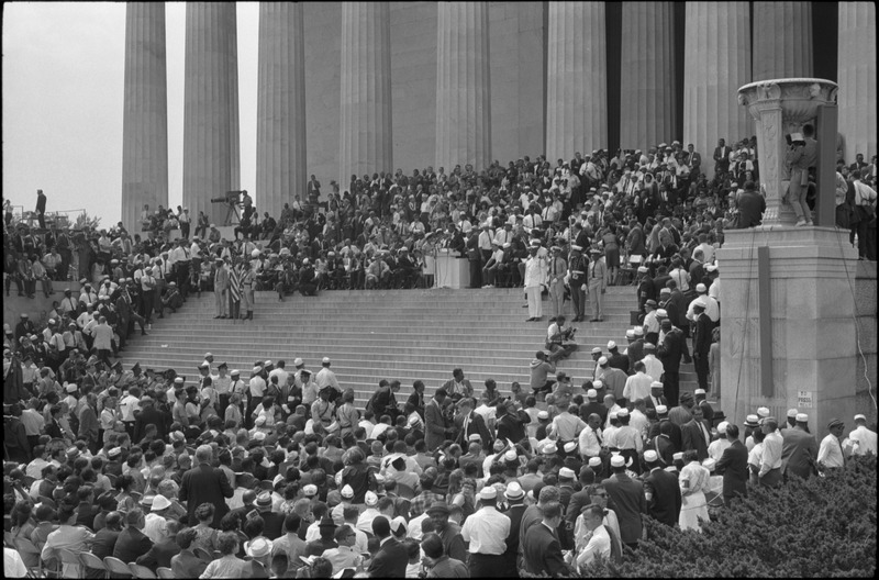 Military color guard on steps of Lincoln Memorial with audience, speakers & photographers on all sides. Photographed by Warren K. Leffler. (Aug. 28, 1963). Source: Library of Congress #LC-DIG-ds-04411.